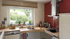 Unterfahrbare Arbeitsfläche abgesenkt mit flacher Spüle, Vorbereiten und Kochen über Eck angeordnet.