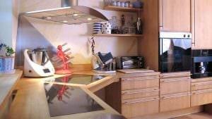 Der in die Massivholzarbeitsplatte flächenbündig eingelassene Granit hat in dieser Küche zwei Funktionen.